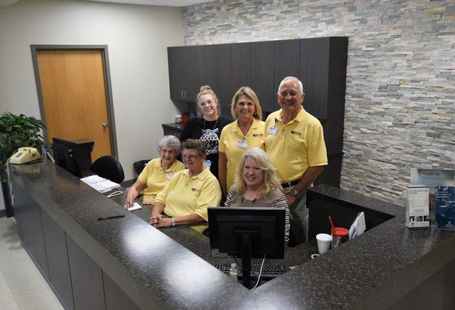 Surgical reception area workers (first row, from left) volunteer Dorthy Patterson, volunteer Karen Hammett, surgical reception coordinator Diane Coackrum, (second row) and surgical reception coordinator Ashton Wilbur (top row, far left) join Gayle and Ed Goodman in the renovated surgical reception area Monday afternoon at Baxter Regional Medical Center.