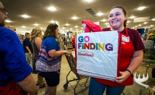 Mia Harris gives shopping bags to customers as HomeGoods opened in The Oaks shopping center in August.