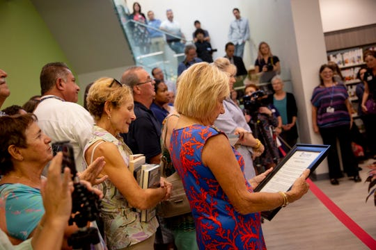 Helena Nesbit, president of Friends of Bonita Springs Library, looks at a proclamation she was presented with during a ribbon-cutting ceremony for the new public library in Bonita Springs on Monday, August 26, 2019.