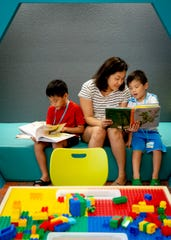 Christina Kim, center, reads with her sons Isaiah Kim, 7, left, and Joshua Kim, 5, right, during the grand opening of the new public library in Bonita Springs on Monday, August 26, 2019.