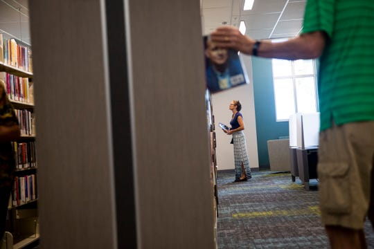 Cindy Salac, center, looks through the stacks of books during the grand opening of the new public library in Bonita Springs on Monday, August 26, 2019.