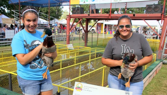 From left, Nicole Jasso, 12, and Lucia Cervantes each took home the winning purse of $1,420 at the 40th annual Great American Duck Race in Deming, NM. Jasso (wet track winner) and Cervantes (dry track winner) weathered 99-degree heat and survived quarter- and semi-final eliminations to cash in.