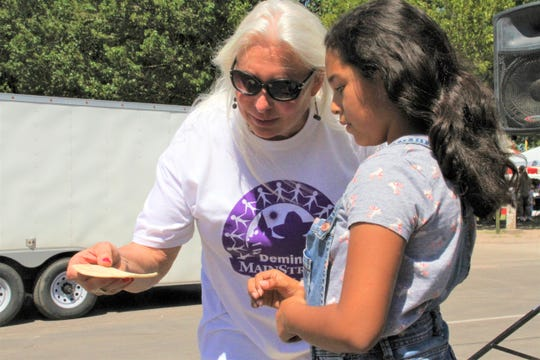 Deming MainStreet Executive Director Christie Ann Harvey goes over tortilla tossing techniques with a young tosserita.