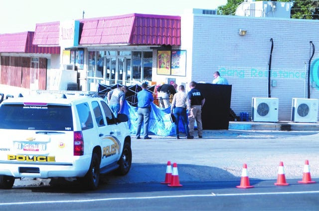Crime scene investigators with the Hobbs Police Department and New Mexico State Police examined the body of Roberto Mata of Carlsbad Friday morning behind a barricade following a shooting with an HPD officer late Thursday night.