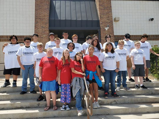 Cyber Patriot Camp participants show off their hard-earned t-shirts.