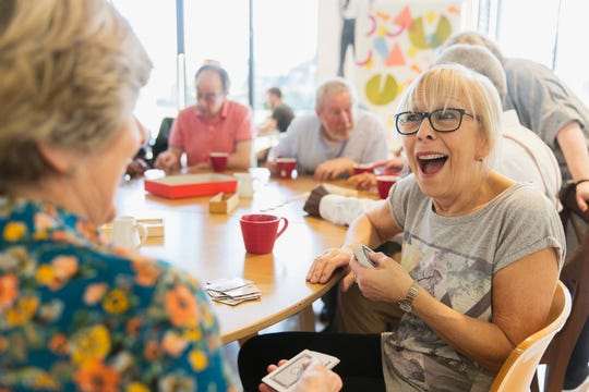 Happy Senior Woman Playing Cards With Friend In Community Center