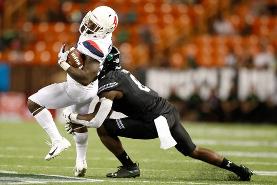 Arizona running back J.J. Taylor (21) tries to get around Hawaii defensive back Eugene Ford (8) in the second half of an NCAA college football game, Saturday, Aug. 24, 2019, in Honolulu.