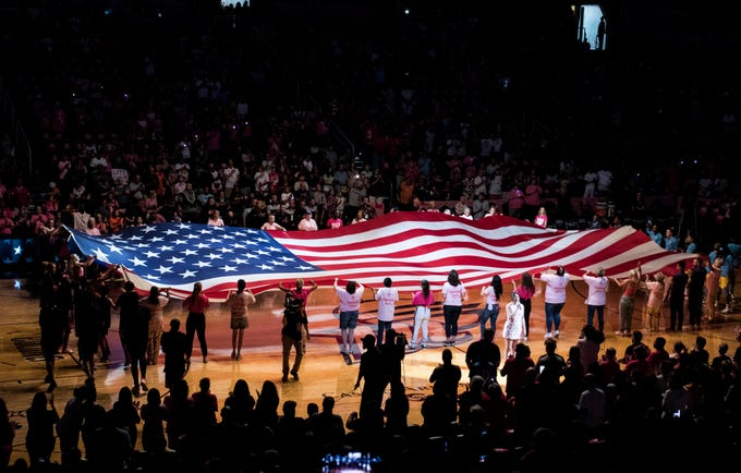 Cancer survivors display the American flag before the Phoenix Mercury Chicago Sky game at Talking Stick Resort Arena on Aug 25, 2019 in Phoenix, Ariz. (Darryl Webb/For the Republic)
