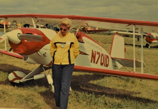 This vintage photo shows Dottie Patrick with the biplane she built at her home. She did some of the work in her garage and some in her living room.