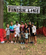 Vassar College cross-country and track coach James McCowan poses with family and friends after completing the Vermont 100 Endurance Race.