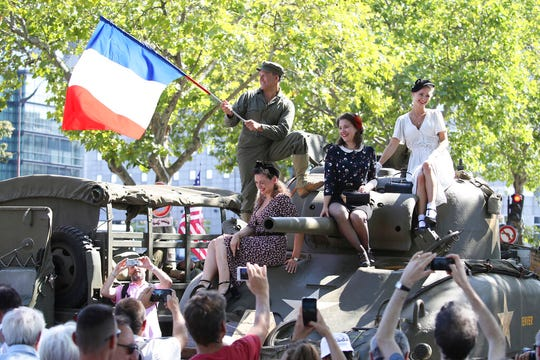 People dressed in World War II era clothes wave to the crowd during celebrations of the liberation of Paris from Nazi occupation 75 years ago, in Paris, Sunday, Aug. 25, 2019. Enthusiasts are retracing the entry of French and U.S. tanks into the city on Aug. 25, 1944. (AP Photo/David Vincent)