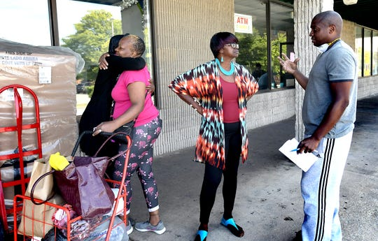 Montika Smith, left, hugs childhood friend Theresa Mix of York City, while Montika's husband Halman Smith II, right, talks with friend Denise Tyler while the Smiths conducted business at their business, Comfort Zone Mattress, at the fire-damaged Yorktown Mall Monday, Aug. 26, 2019. Fire damaged several businesses there after a fire occurred early Friday, Aug. 23. Bill Kalina photo