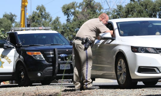 California Highway Patrol officer Jason Morton tickets a driver on Interstate 5 who went over the 55-mph speed limit on Monday, Aug. 26, 2019, in the work zone of the Redding to Anderson six-lane expansion project.