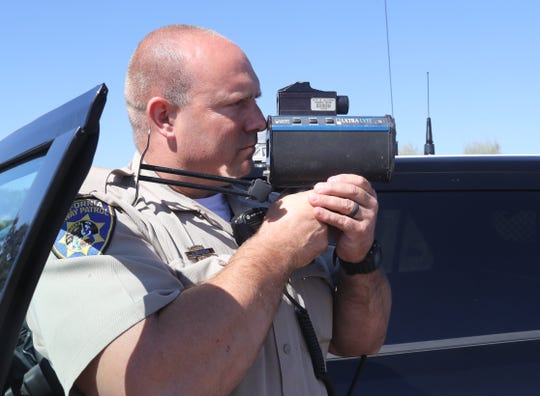 California Highway Patrol officer Jason Morton points a laser speed gun at Interstate 5 traffic on Monday, Aug. 26, 2019, to catch drivers going over the 55-mph speed limit in the work zone of the Redding to Anderson six-lane expansion project.