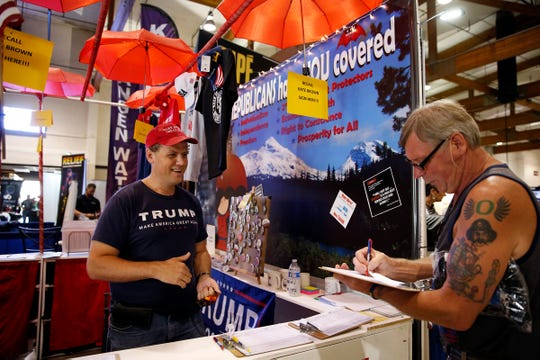 Mark Callahan (left), vice-chair of the Clackamas County Republican Party, talks with Jim Drago of Salem as he signs one of the four petitions being offered at the Oregon GOP's booth at the Oregon State Fair in Salem, Oregon, on Saturday, Aug. 24, 2019. The petitions include two separate recalls of Gov. Kate Brown.