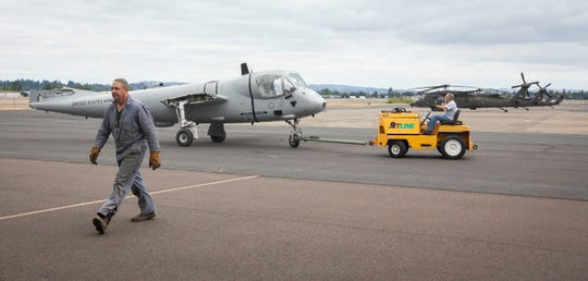 Grant Rush, of Lyons, walks back to the hanger from the aircraft tug as he works to get an OV-1 Mohawk surveillance aircraft turned around so the crew can install the second wing in Salem, August 17, 2019. Volunteers are restoring the aircraft that is scheduled to be installed for public display at the Salem airport in September.