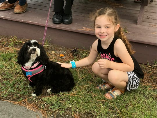 Ember Coates, 4, who is visiting from Pennsylvania, poses with Joy, a 5-year-old Havenese, before a dedication ceremony for the new dog park on Chincoteague, Virginia on Monday, Aug. 26, 2019.