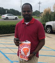 Shreveport's William Moore nabs the first Popeyes chicken sandwiches available in the area Monday.