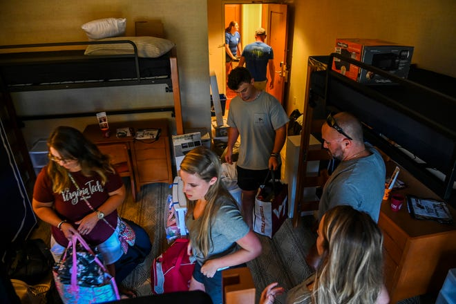"Tori Davis, center, and her roommate, Emily Moore, right, both from Danville, Virginia, move into their room at the Inn at Virginia Tech University with the help of Emily's family on Wednesday, Aug. 21, 2019, in Blacksburg, Virginia. The Inn is a campus hotel that has been temporarily converted into dorm rooms because Virginia Tech has seen a surge in enrollment and is facing a student housing crunch. The university is leasing two nearby motels to house students and have a dorm under construction. Emily's mother, Wendy Moss, left, said, ""I think it worked out for the good, I mean, for them to still be on campus and they actually have some luxuries of being in a hotel. They have their own bathroom, air conditioning and all that."""