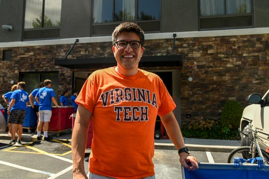 Juan Espinoza, director of admissions at Virginia Tech University, waits to help incoming students move into HIE (Holiday Inn Express) student housing near Virginia Tech University on Wednesday, Aug. 21, 2019, in Blacksburg, Virginia. The hotel has been leased by the university for dorm rooms because Virginia Tech has seen a surge in enrollment and is facing a student housing crunch. The university is leasing two nearby motels to house students and has a dorm under construction.