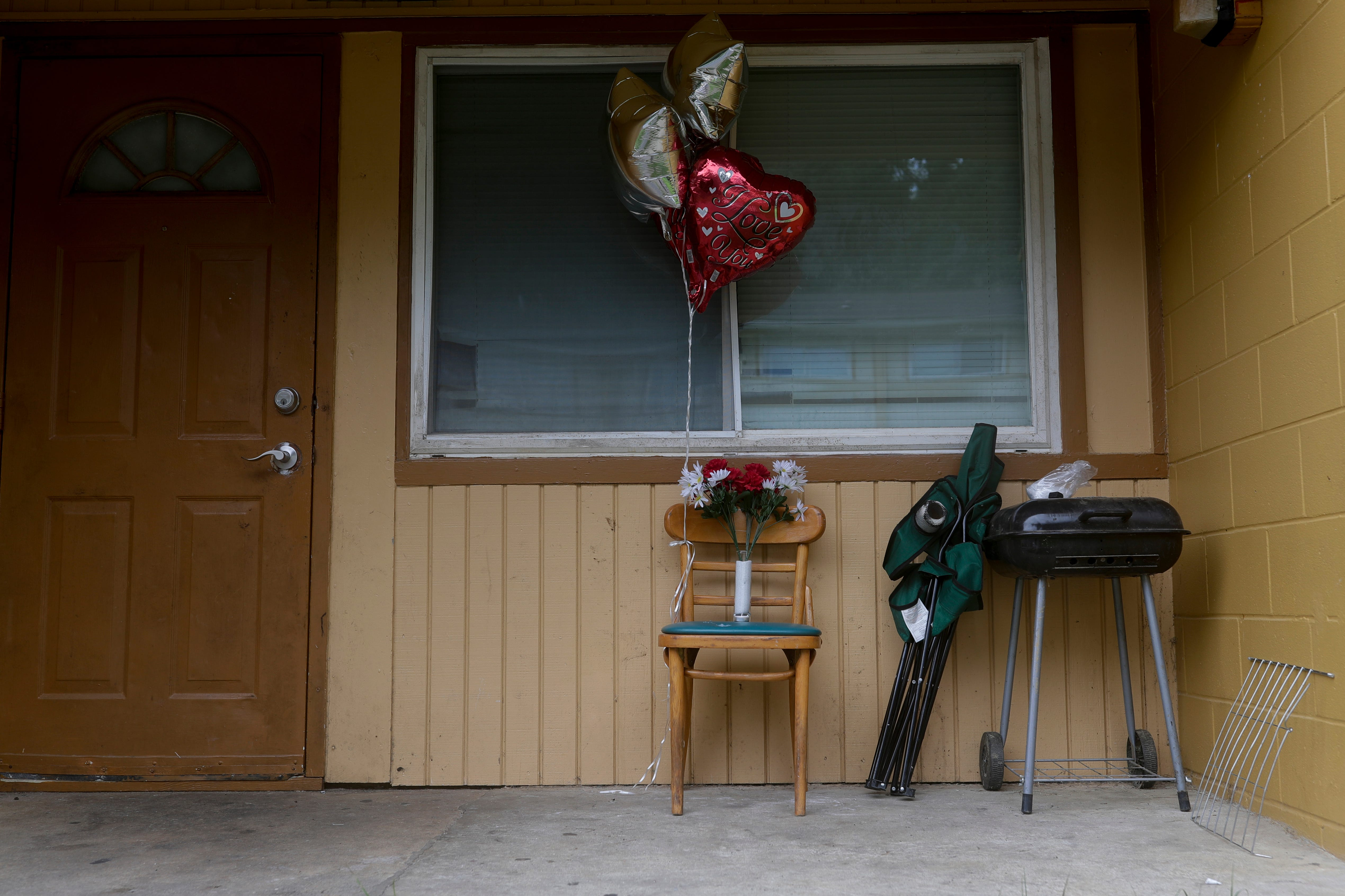 Balloons, a single candle and a bouquet of plastic flowers are placed on the front porch of a Springfield Apartments building where the victim of a Friday night shooting lived.