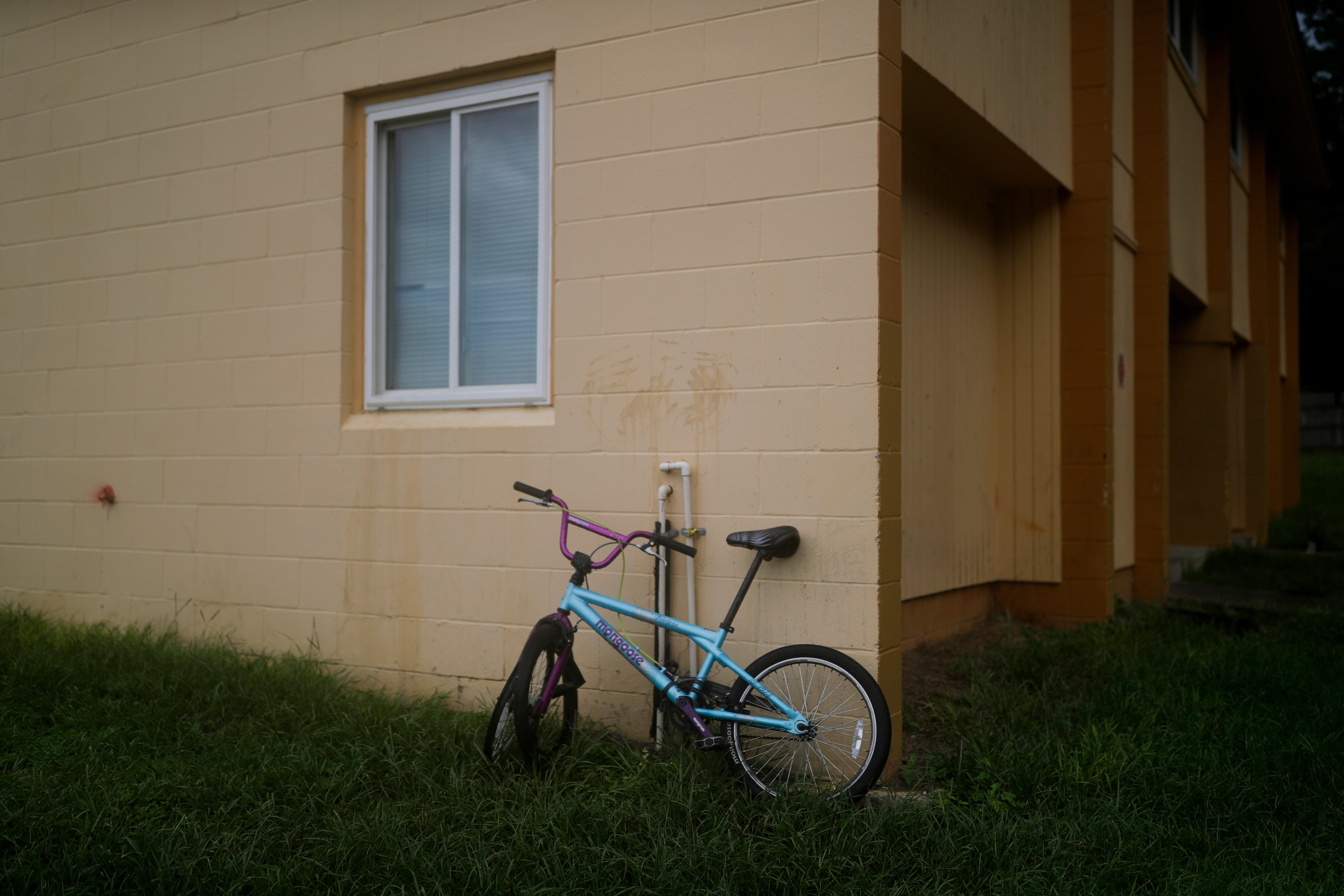 A children's bicycle leans against an apartment building where the victim of a Friday night shooting lived at the Springfield Apartments on Joe Louis Street.