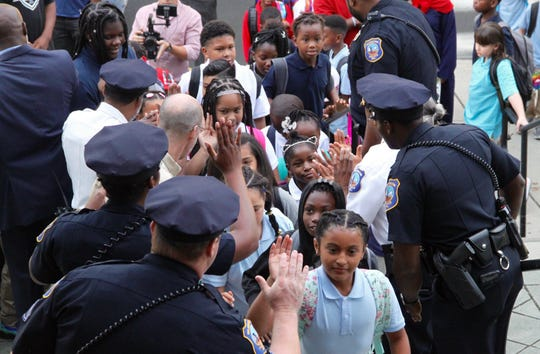A line of Wilmington police officers, politicians and volunteers high-five Warner Elementary School students to welcome them back to school on Aug. 26, 2019.