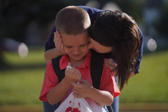 Kash Gast gets a kiss goodbye from his mother Leah Taylor while dropping him off for the first day of school at Marbrook Elementary School on Monday morning.