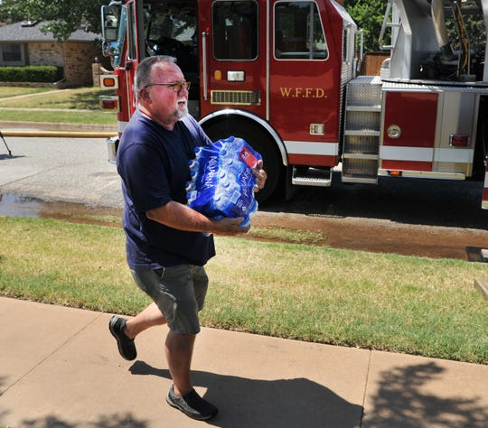 Neighbors brought water and ice to help firefighters, fighting a house on Belinda Dr., stay hydrated and cool, Monday afternoon after the Wichita Falls Fire Department worked to control a 3-alarm house fire that left 5-people in need of the American Red Cross assistants.