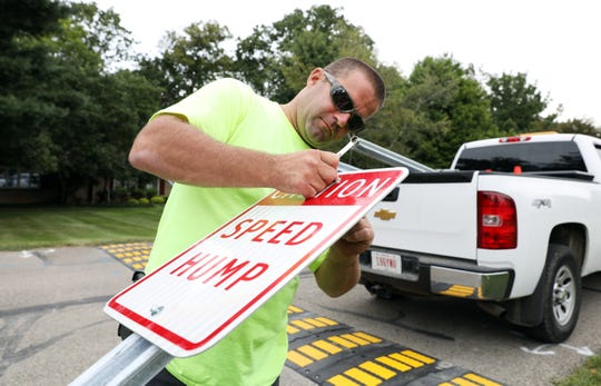 Heath Daniel of the Zanesville Street Department installes a speed hump sign on Rankin Drive in Zanesville Monday morning.