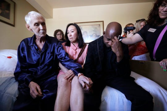 In this May 10, 2019, photo, Robert Fuller, left, consoles friends gathered on and near his bed as he makes his final preparations before dying, in Seattle.