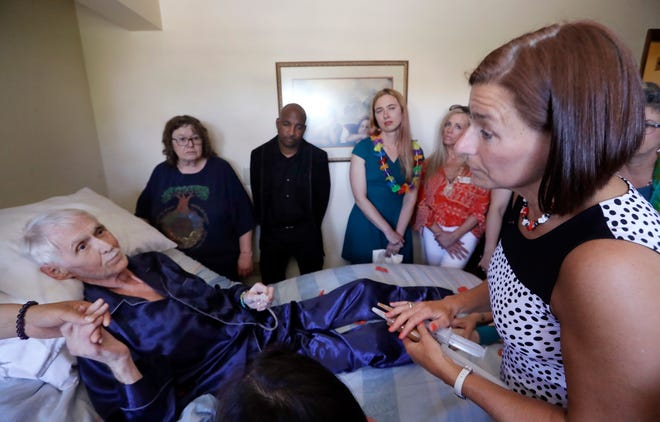 In this May 10, 2019, photo, End of Life Washington volunteer Stephanie Murray, right, brings the drugs that will end the life of Robert Fuller to him as he lies in bed, in Seattle. Earlier in the day, Fuller had the party of a lifetime. He's one of about 1,200 people who have used Washington's Death with Dignity Act to end their lives in the decade since it became law.
