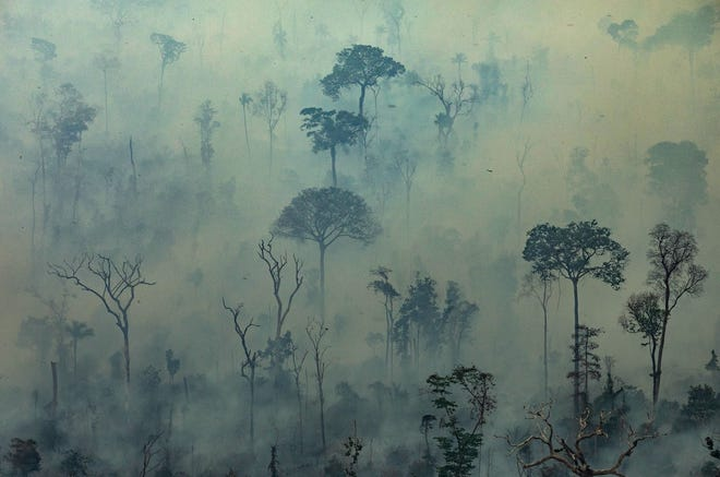 Smoke billows from fires in the forest in the Amazon biome in the municipality of Altamira, Para State, Brazil, on August 23, 2019.