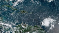 A satellite image taken Monday morning, August 26, 2019, shows Tropical Storm Dorian (right) approaching the Windward Islands of the Caribbean.