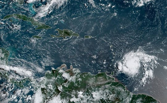 A satellite image taken Aug, 26, 2019, shows Tropical Storm Dorian (right) approaching the Windward Islands of the Caribbean.