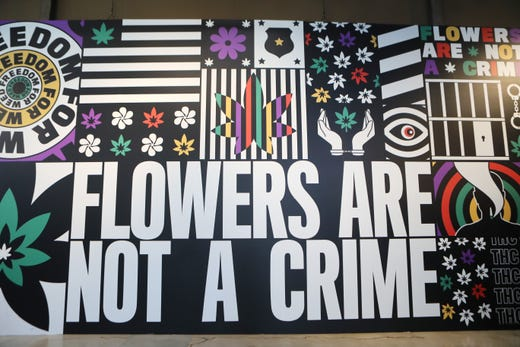 """The phrase """"Flowers Are Not a Crime"""" is displayed along with other pro-marijuana slogans at the Weedmaps Museum of Weed."""
