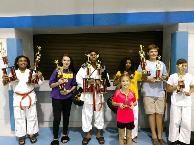 Members of George Johnson's American Black Belt Academy display their championship trophies at the Battle of the South Karate Tournament in Mandeville Aug. 24.