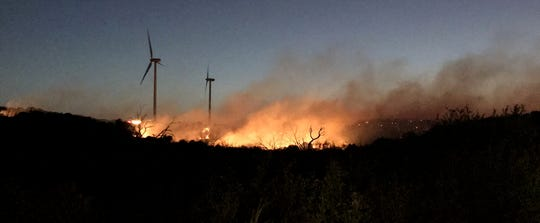 Flames from the Rhodes Ranch 3 Fire burn near wind turbines on Monday.