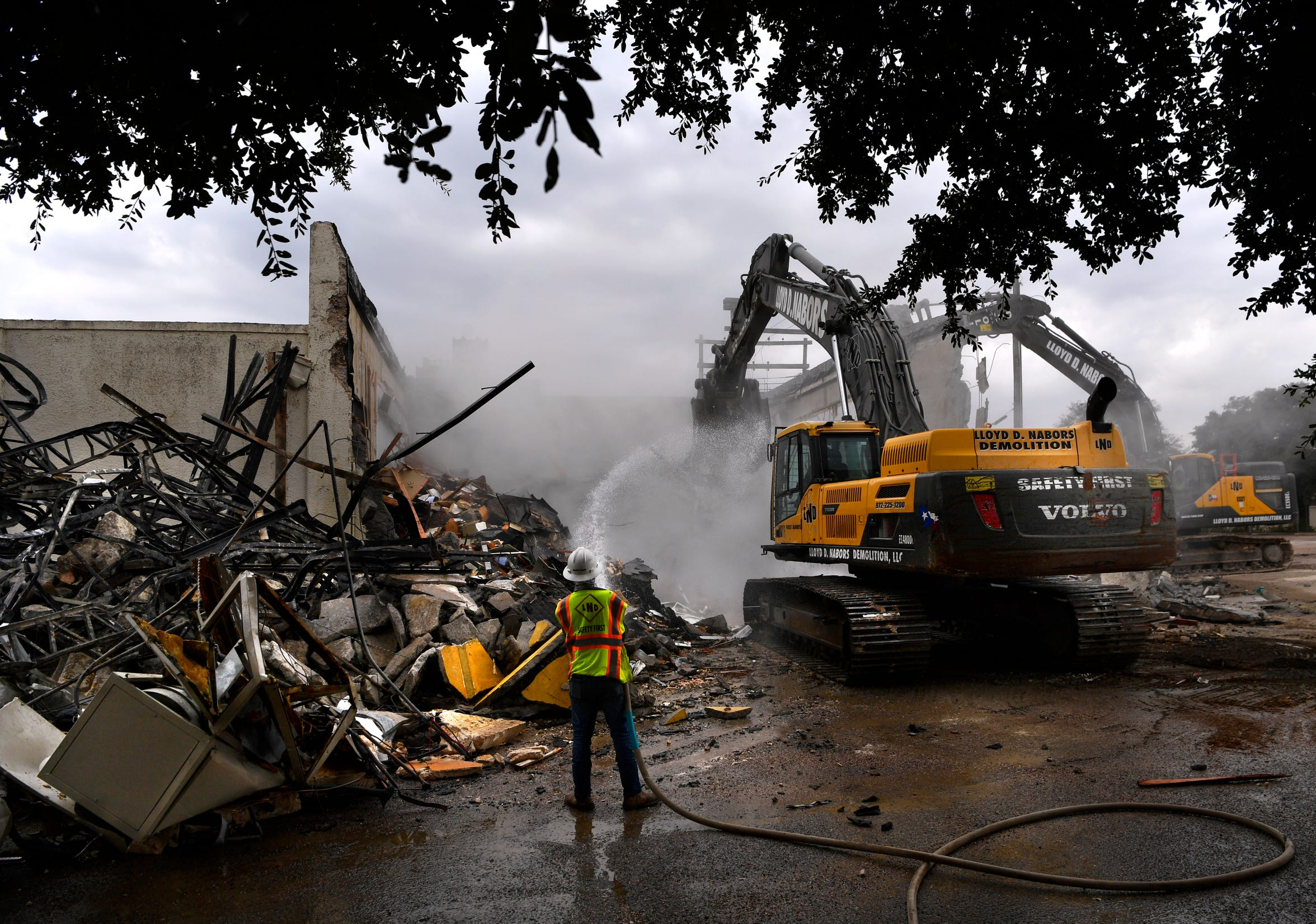 A worker hosed down the dust during demolition of the old Abilene Water Department building in the 1100 block of North Sixth Street Aug. 27.
