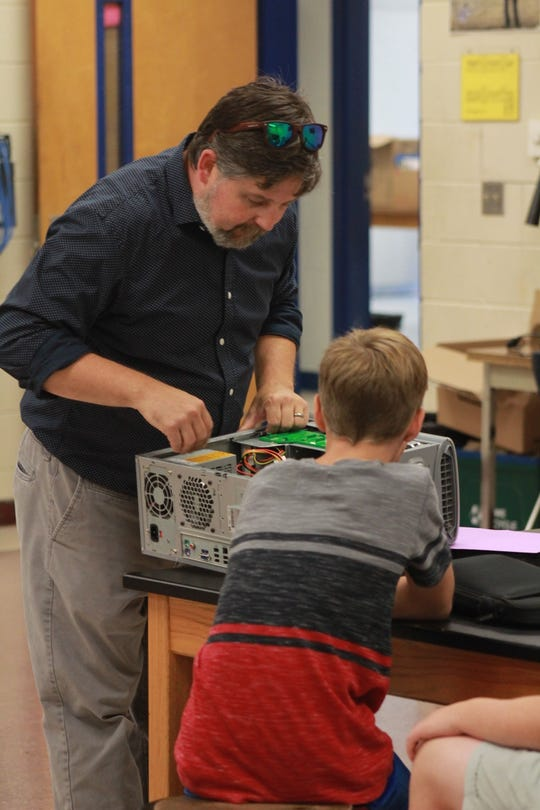 Tommy Hicks, named Teacher of the Year for Madison County Schools, shows off the inside of a computer to a 7th grader.