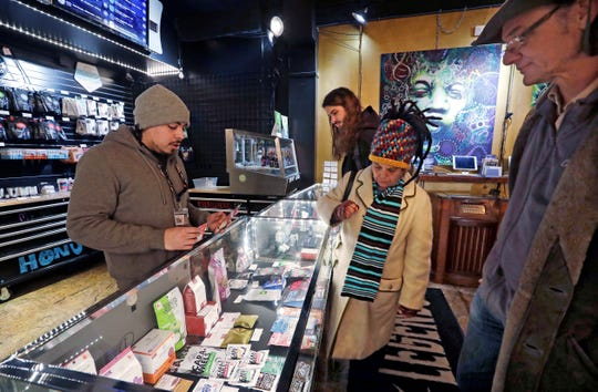 FILE - In this Jan. 4, 2018, file photo, cannabis consultant Juan Aguilar, left, assists customers Bill, right, and Nize Nylen and their son Russell shop for edible marijuana products in the Herban Legends pot shop in Seattle.