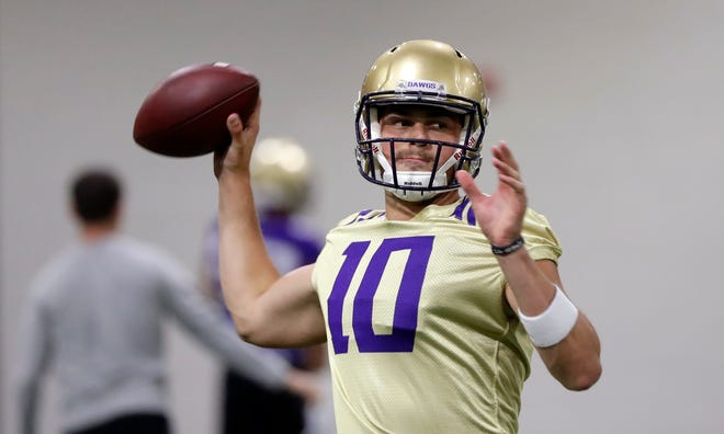 In this Aug. 5, 2019, file photo, Washington quarterback Jacob Eason readies a throw during an NCAA football practice in Seattle. With Jake Haener announcing over the weekend he is leaving the program, Jacob Sirmon is  now the backup quarterback.
