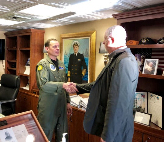 Capt. Max Clark, left, commanding officer of the USS Nimitz, shakes hands with Greg Mason as a portrait of Chester W. Nimitz hangs in the background Tuesday. Mason gave to the ship a letter Nimitz wrote to his grandfather in recognition of his heroism at Pearl Harbor on Dec. 7, 1941.