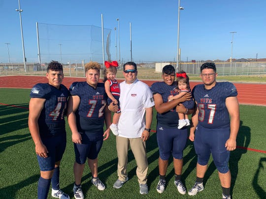 Veterans Memorial defensive line coach James Villarreal stands with his two daughters and some of his players.