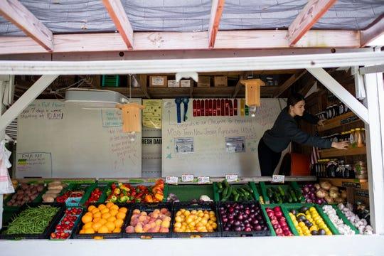 Cheyenne Higginbotham, 15, works the produce stand Monday, Aug. 26, 2019 in Evesham, N.J.
