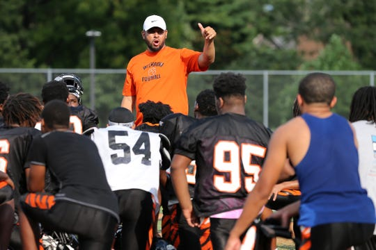 Withrow High School head football coach Kali Jones instructs the team at the conclusion of practice, Wednesday, Aug. 14, 2019, at Withrow High School in Cincinnati.
