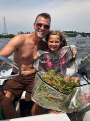 The Department of Environment, Great Lakes, and Energy's Kevin Walters and family collect a mat of European frogbit from the lower Grand River for verification in August 2019.