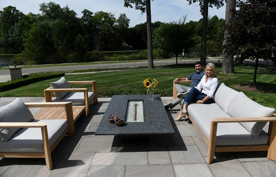 From left, developer, builder and homeowner Arya Afrakhteh and designer Katie Rodriguez sit on the natural stone patio of the Birmingham house.