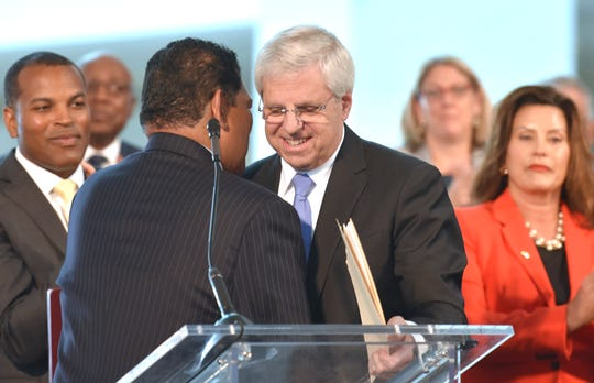 Larry Alexander, left, president and CEO of the Detroit Metro Convention and Visitors Bureau and chair of the Detroit Regional Convention Facility Authority, welcomes Gary Torgow, right, executive chairman of TCF Financial Corporation, to the podium Tuesday.