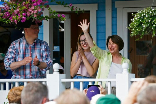In this Aug 22, 2019 photo, Democratic presidential candidate Sen. Amy Klobuchar, D-Minn., addresses fair goers from her fair booth during a campaign visit to the Minnesota State Fair in Falcon Heights, Minn. With her, left, is husband John and daughter Abigail.